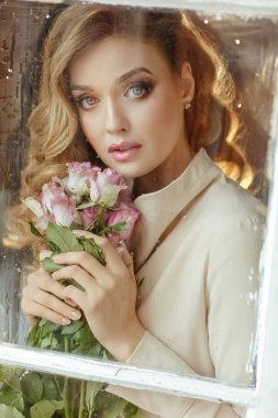 Portrait of a beautiful delicate sensual blonde girl with roses,
