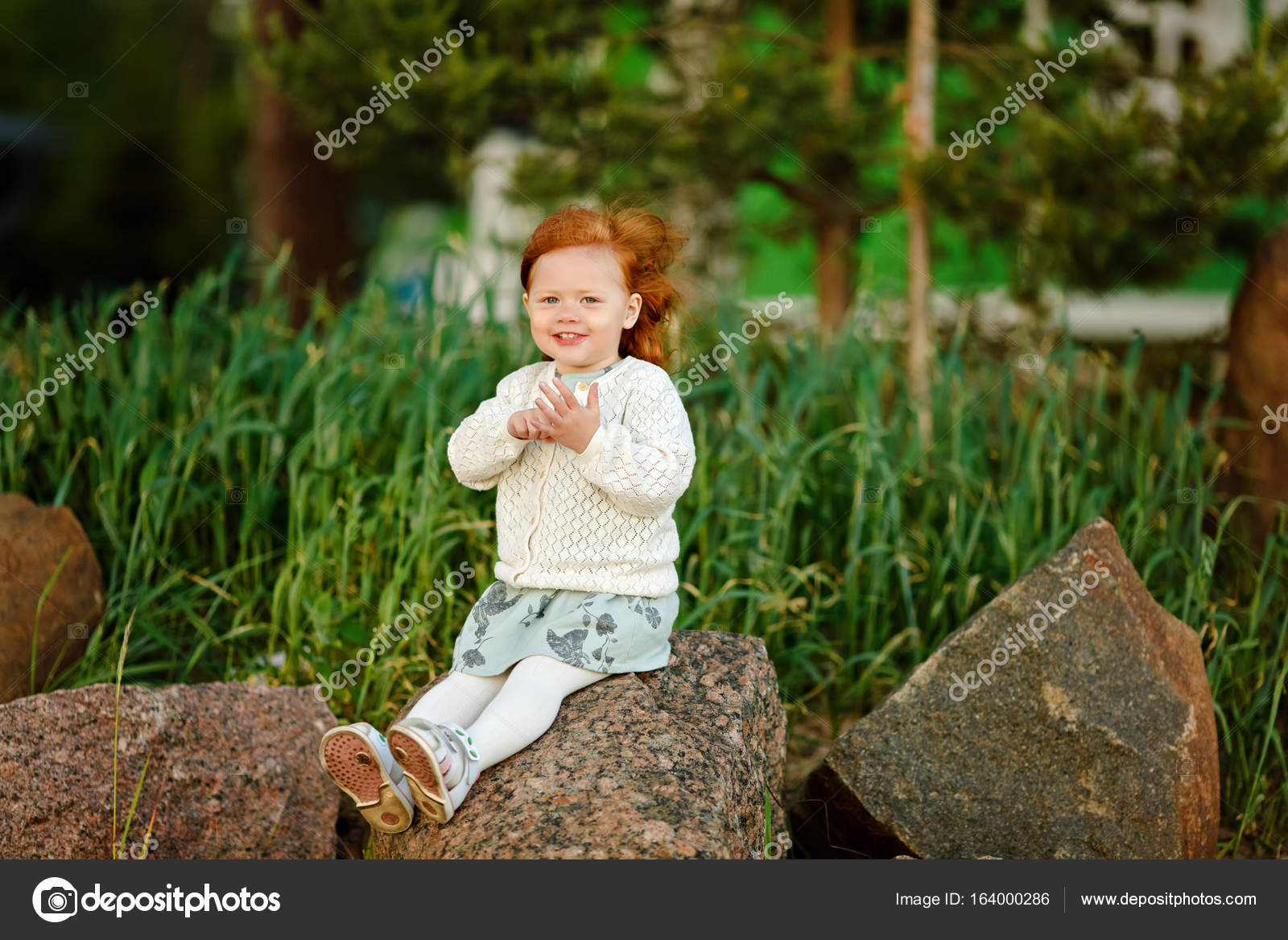 little beautiful red-haired girl baby girl smiling, sitting on s