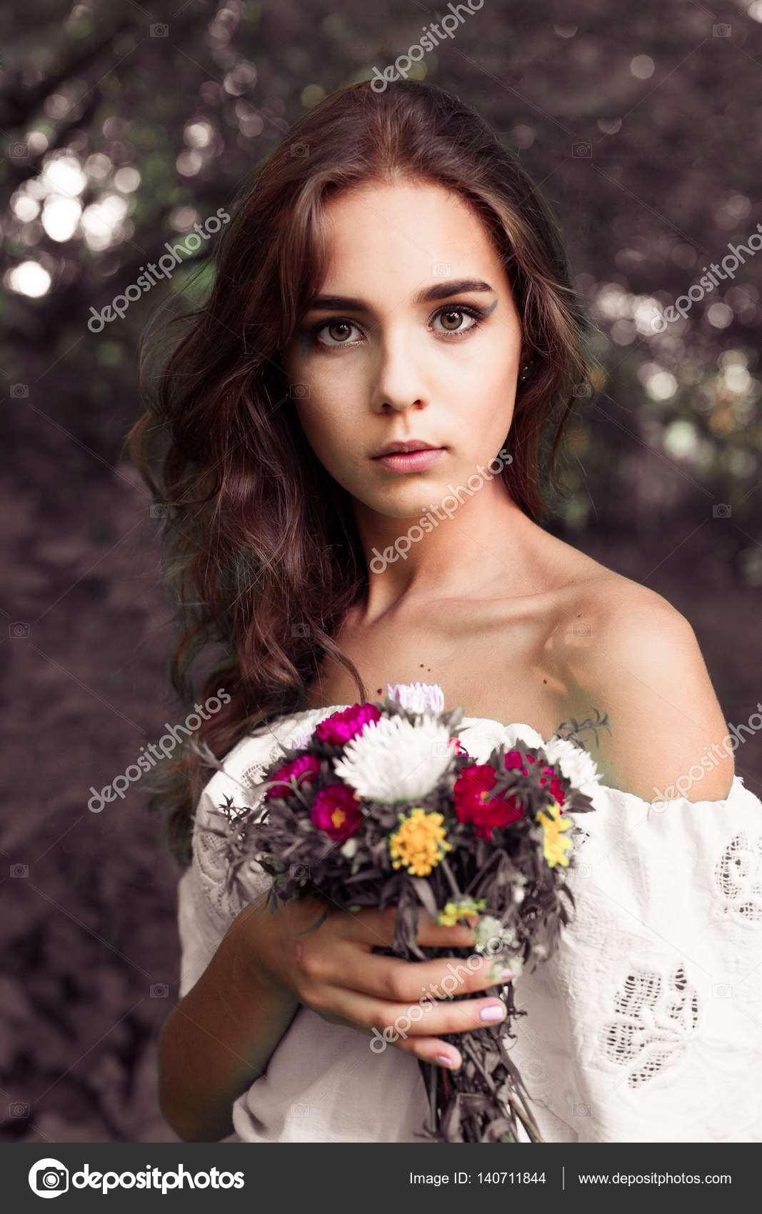 Beautiful young girl with a bouquet of flowers beautiful young beautiful young girl with a bouquet of flowers beautiful young woman in nice blue dress posing on colorful wall of flowers fashion photo nice hair izmirmasajfo