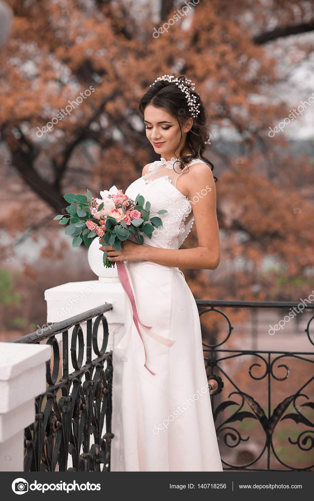Novia hermosa con vestido blanco elegante con un ramo de flores en ...