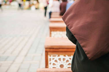 Conceptual photo of a woman wearing a hijab sitting in the Sultanahmet Square in Istanbul, Turkey.