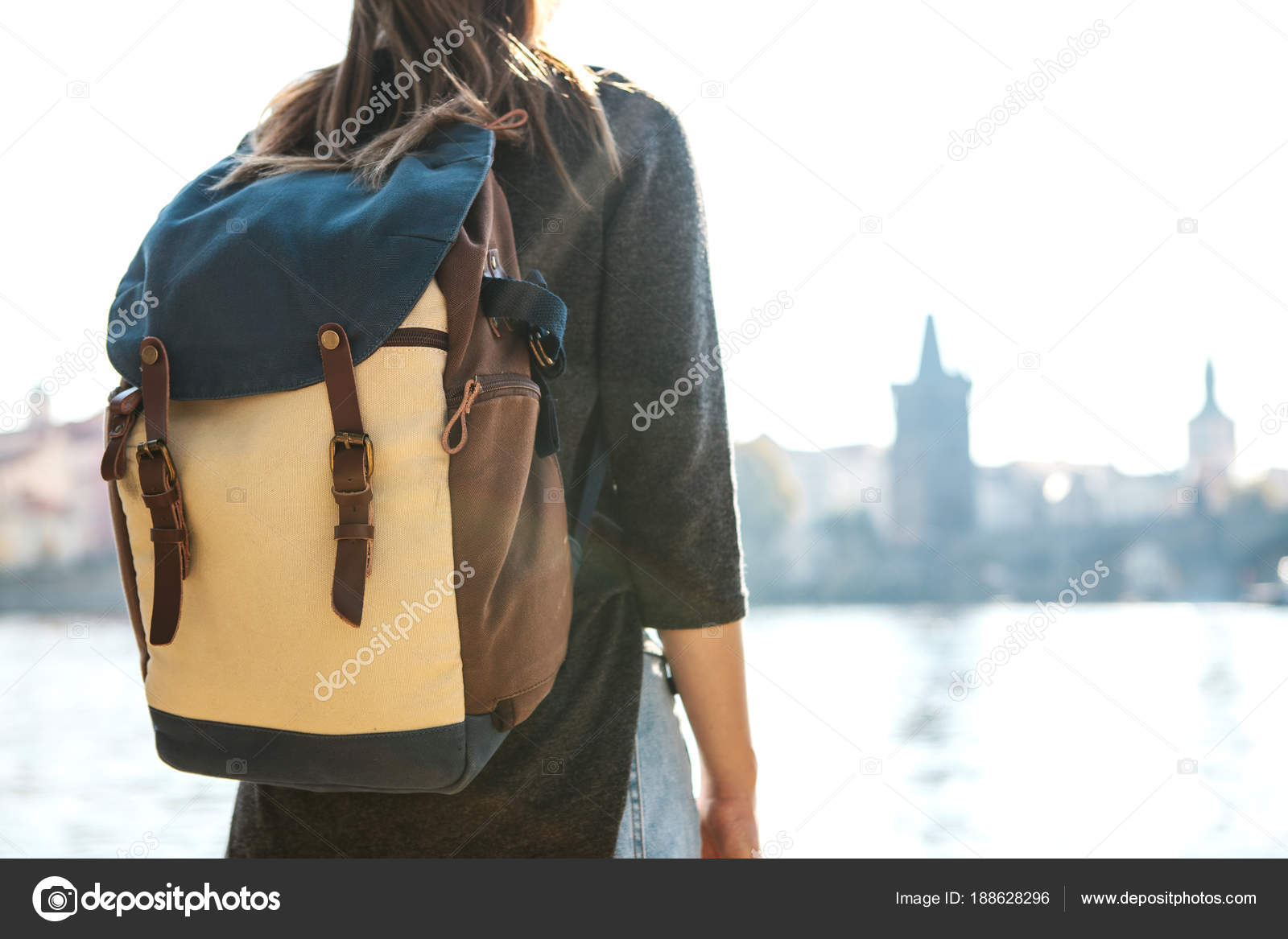ad4e7456fe7b A beautiful young tourist girl with a backpack stands next to the Vltava  river in Prague and admires one of the most popular attractions called the  Charles ...