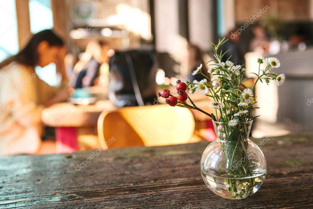 A vase with flowers on a wooden table in the foreground, a person working in the background is defocused.