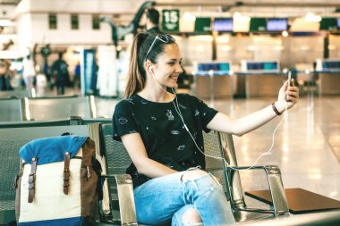 Girl tourist or student talking on video chat or video call while waiting for a flight at the airport.