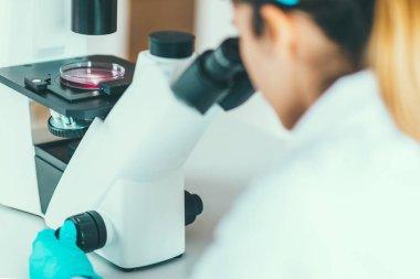 Biotechnology researcher using microscope