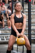 Photo Woman working out with kettlebell at a cross training competition