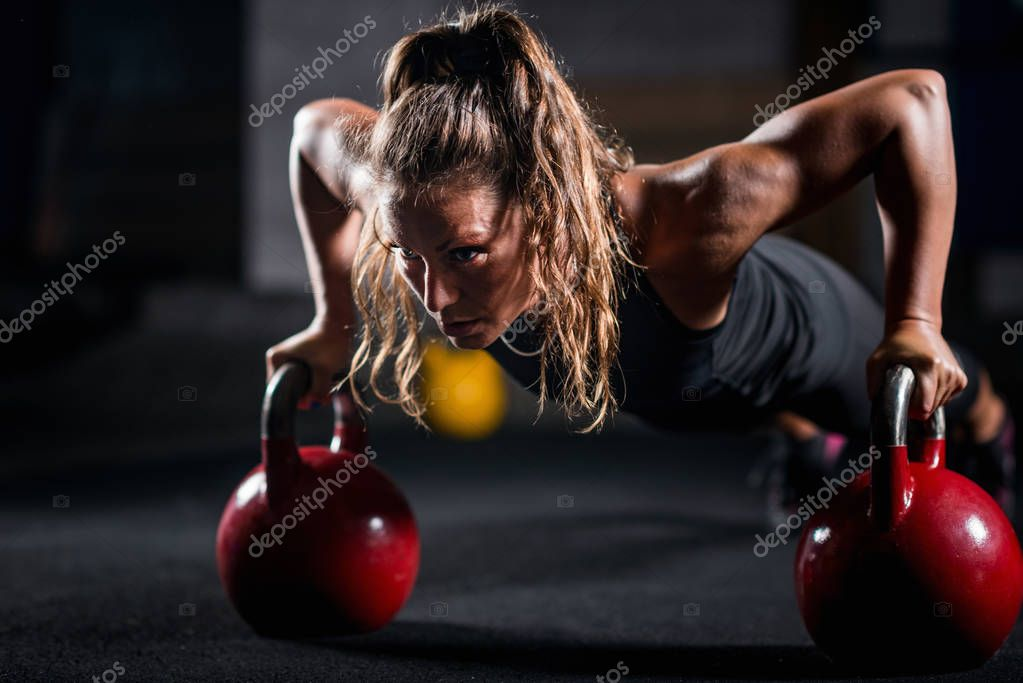 Woman athlete exercising with kettlebells indoors