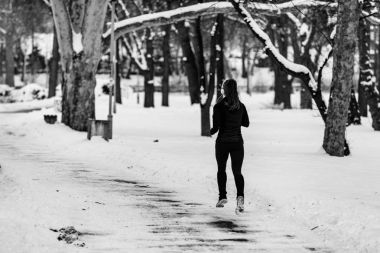 Female athlete jogging in the park on winter day in park