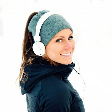 Female athlete portrait in park in winter with snow around the park, Listeninig music