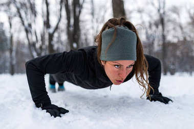 Female athlete exercising in park on winter day. Listening music and exercising