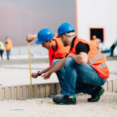 Construction workers measuring on construction site