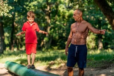 Grandfather and grandson walking on wooden huddle in park
