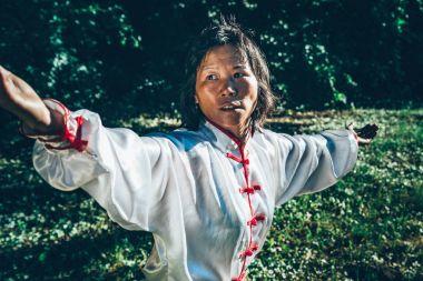 Asian woman practicing Tai Chi outdoors