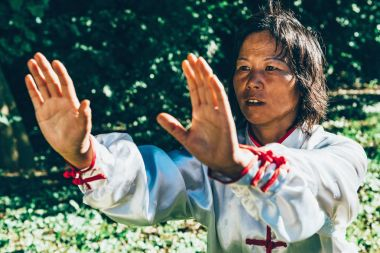 Asian woman practicing Tai Chi outdoors