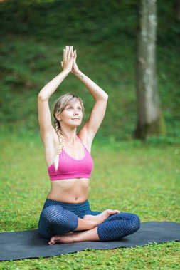 Beautiful young woman doing yoga, hands in prayer position
