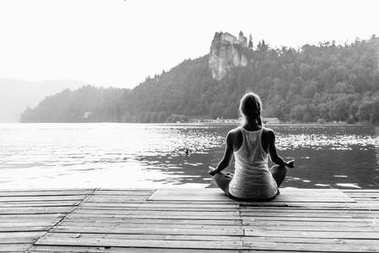 Female in lotus position. Meditating by the lake