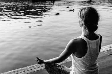 Woman in lotus positing practicing yoga on lake