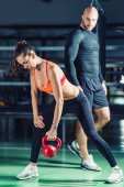 Photo Personal trainer exercising with kettlebell with woman in the gym