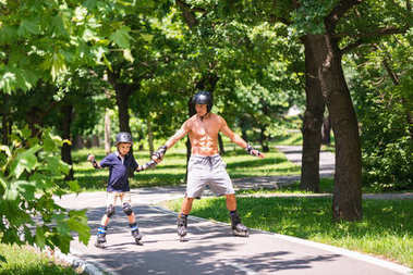 Little boy roller skating in the park with his grandfather