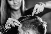 Fotografie Hair styling man in hairsalon by female hairdresser