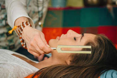 woman using Tuning fork in sound therapy