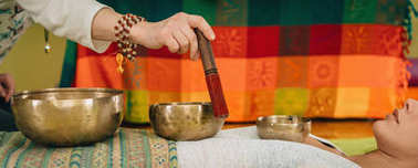 woman using Tibetan singing bowls in sound therapy