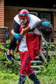Záchranář evakuovat ženské oběti z domu