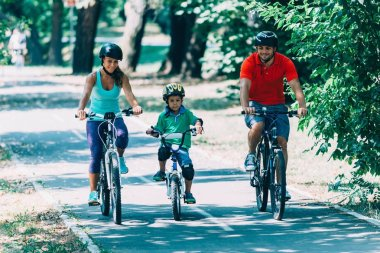 Cheerful family biking in park