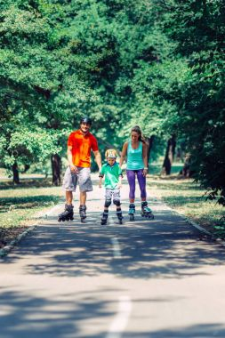 Family with one child roller skating in park