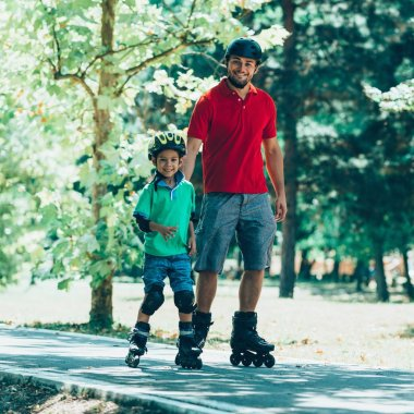 Father teaching son roller skating in park