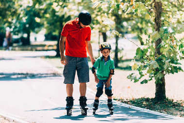 Father and son roller skating in park