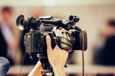 TV camera recording press conference