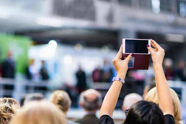 woman recording event with smartphone at political event