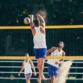 Photo Male team playing beach volleyball