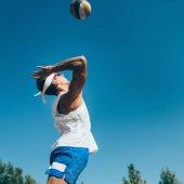 Fotografie Beach volejbalový hráč udeří míč