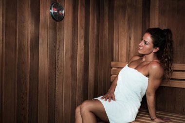 Woman with Towel Sitting on a Bench and Relaxing in Hot Sauna.