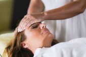 Photo Reiki Therapist Transferring Energy. Peaceful Woman Lying with Her Eyes Closed.