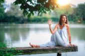 Photo Young woman doing seated spinal twist by the lake. Ardha Matsyendrasana