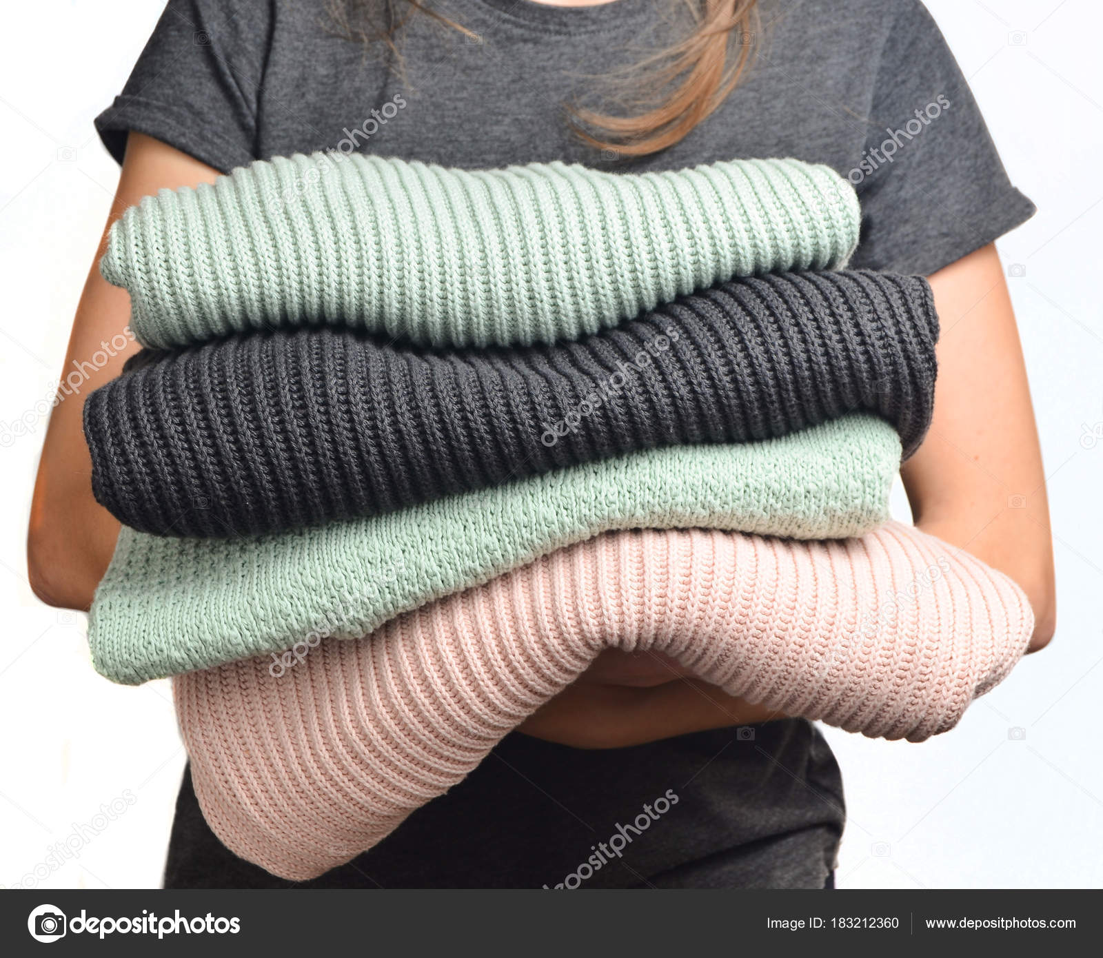 82eef213f1c3 Μια στοίβα των πουλόβερ σε γυναικεία χέρια που απομονώνονται σε λευκό φόντο  — Εικόνα από split271992.gmail.com