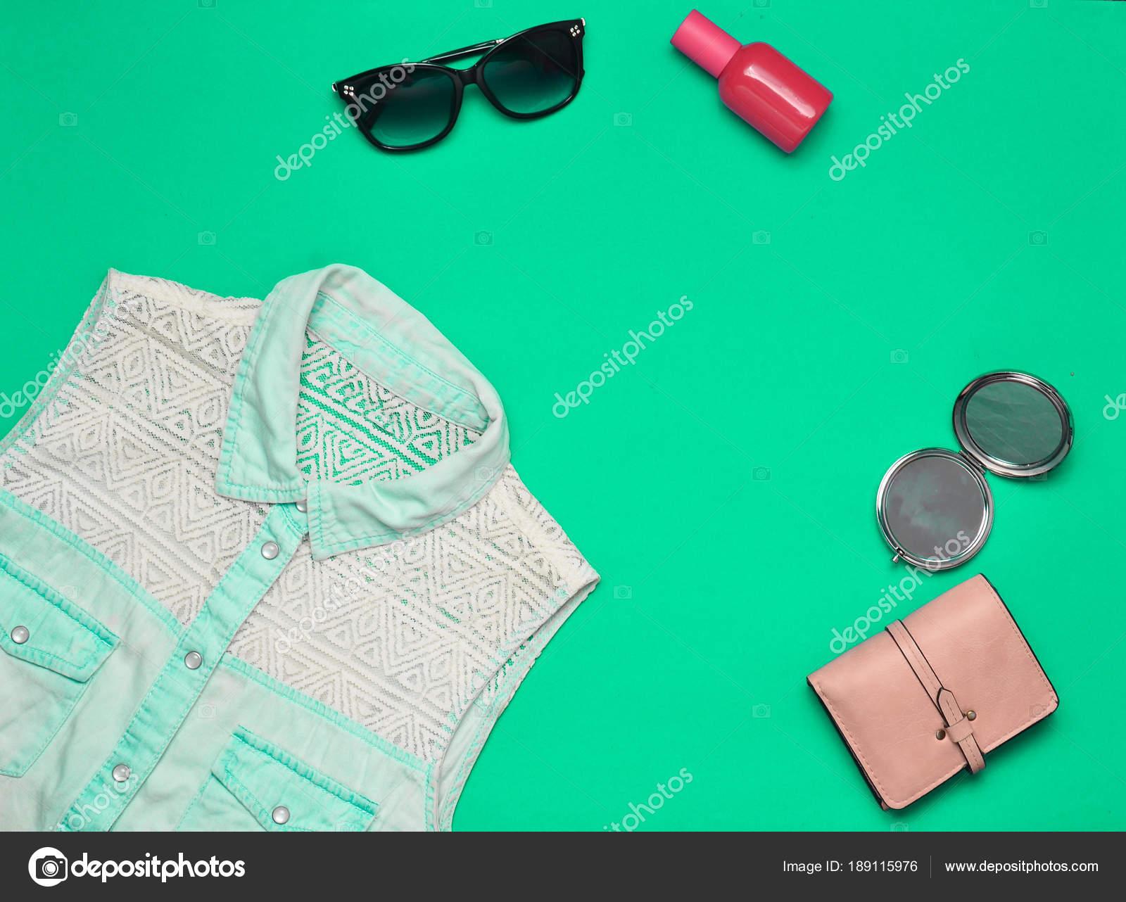 59e8868982c4 Acessórios e roupas em um fundo turquesa feminino. Camisa jeans, espelho,  frasco de perfume, óculos de sol, bolsa. Copie o espaço. Plano de leigos.