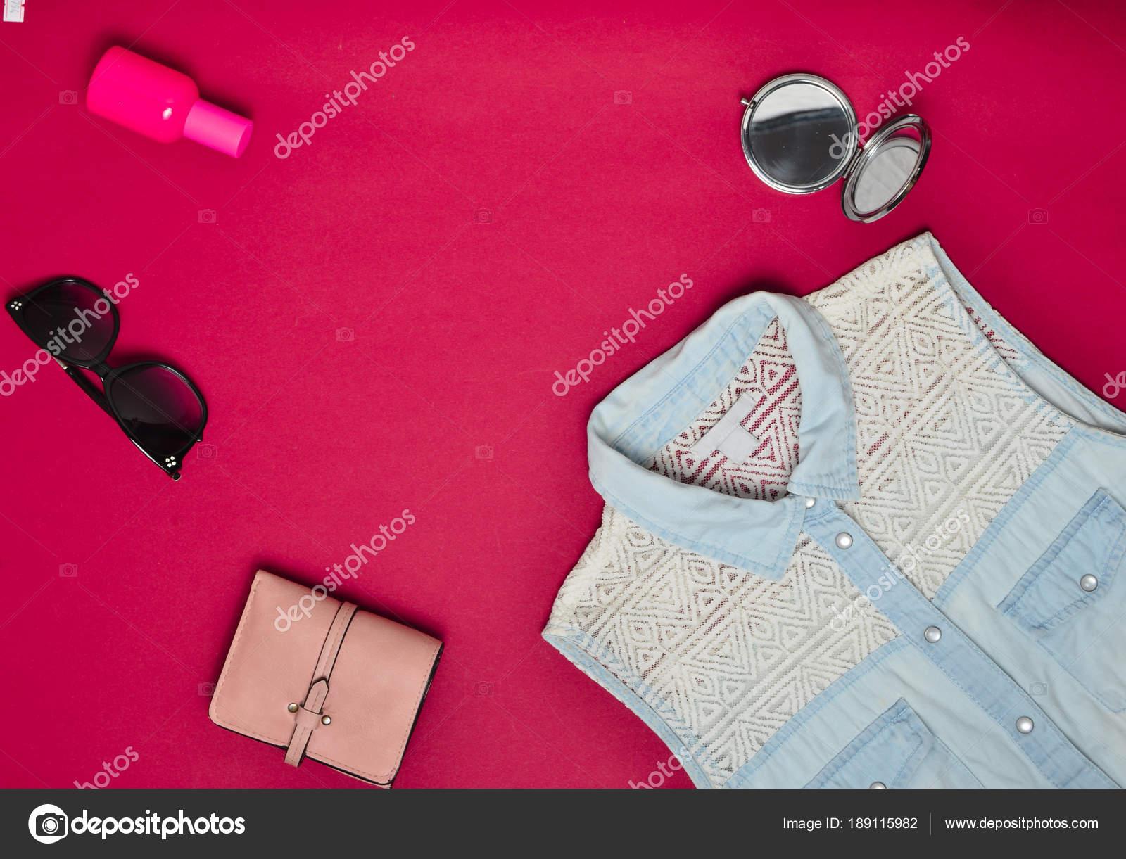 fe504931c05b Feminina acessórios e roupas em um fundo vermelho. Camisa jeans, espelho,  frasco de perfume, óculos de sol, bolsa. Copie o espaço. Plano de leigos.