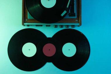 Retro vinyl record player. Vinyl records. Neon light, top view