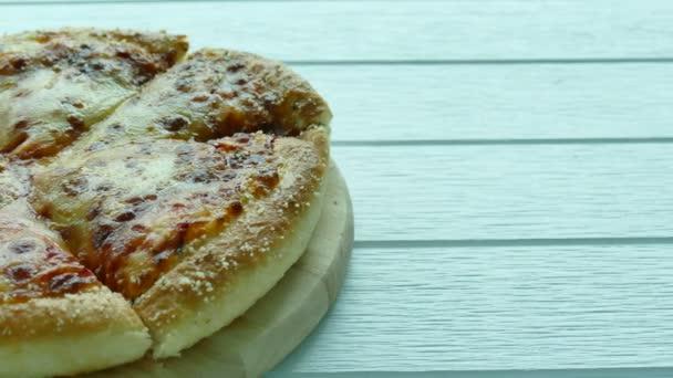 Krájené pizzy na dřevěné desce