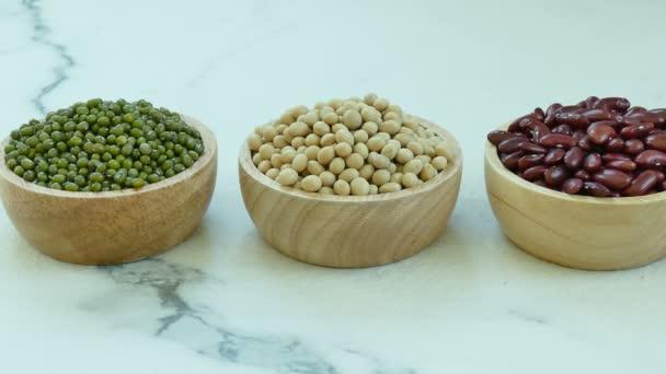 Auswahl der Bohnen in kleine Holzschalen: rote Bohnen, Sojabohnen, Mungobohnen