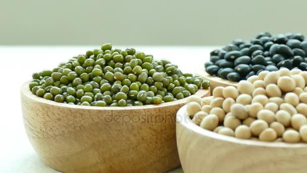 Sortiment Bohnen in kleinen Holzschalen: schwarze Bohnen, Sojabohnen, Mungbohnen