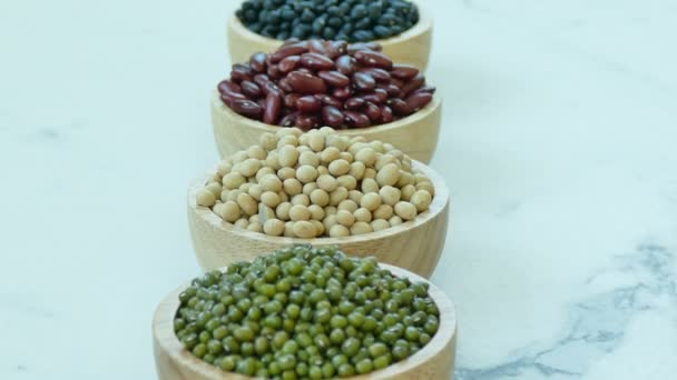 Sortiment Bohnen in kleinen Holzschalen: rote und schwarze Bohnen, Sojabohnen, Mungbohnen