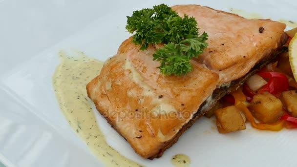 leckeres Lachssteak vom Grill mit Gemüse auf weißem Teller
