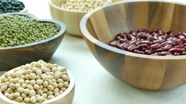Auswahl der Bohnen in kleine Holzschalen: rote und schwarze Bohnen, Sojabohnen, Mungobohnen
