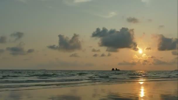 Západ slunce z mořských vln, písečné pláže a zamračená obloha