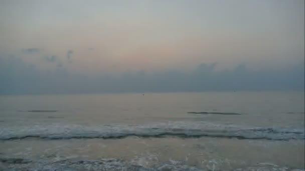 Západ slunce z mořských vln, písečná pláž a dramatické nebe, časová prodleva